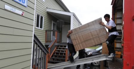 Movers carrying furniture into a house